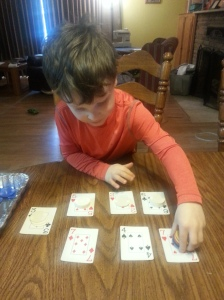 Josiah using his poker chip counters and cards to practice his numbers.